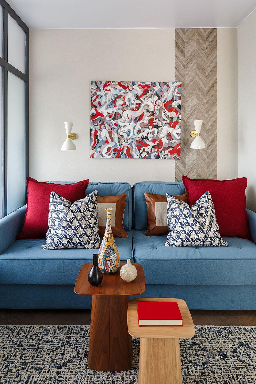 Din bucătărie primul loc care se vede este cel al canapelei, un model care se extinde, realizat pe comandă. În lateralele peretelui sunt fâșii de tapet ce imită desenul parchetului, ca și cum pardoseala ar fi urcată pe verticală. Canapeaua este folosită ca loc de dormit pentru fiul adolescent care vine în vizită. Măsuțele sunt de la Repeat Story, covorul și pernele decorative de la Barel, iar tabloul este semnat de Renata Semenov și achiziționat de la galeria Art Brut Moscova.