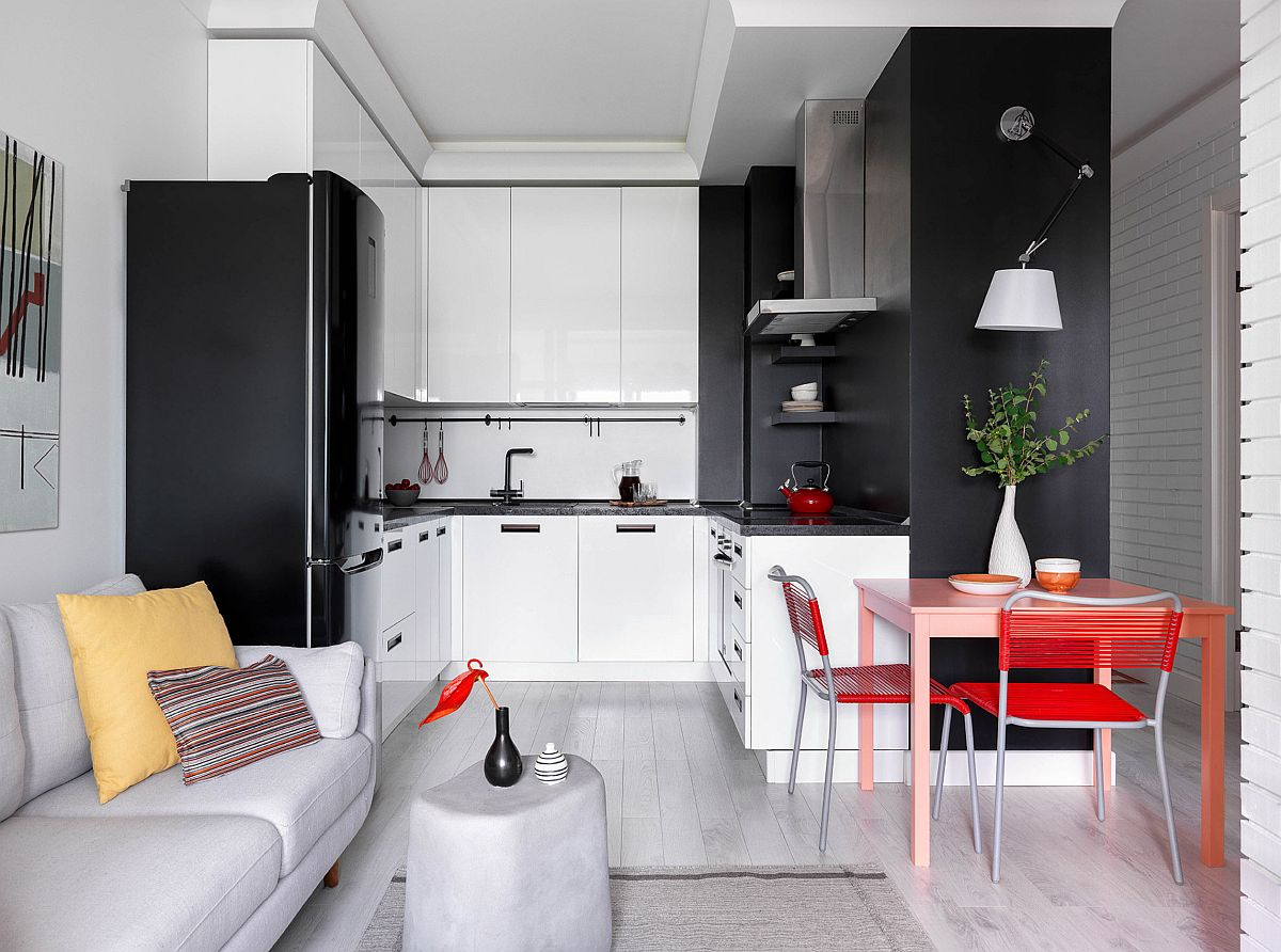 Bucătăria este generos gândită, având în vedere spațiul mic al locuinței. Și asta pentru că familia care locuiește aici gătește des. Corpurile suspendate sunt înalte pentru extra depozitare, iar iluminatul la nivelul plafonului este realizat difuz prin benzi LED integrate în spatele profilelor decorative de tip cornișă.Astfel, fără corpuri de iluminat centrale sau suspendate, senzația de spațiu ordonat este mai accentuată.