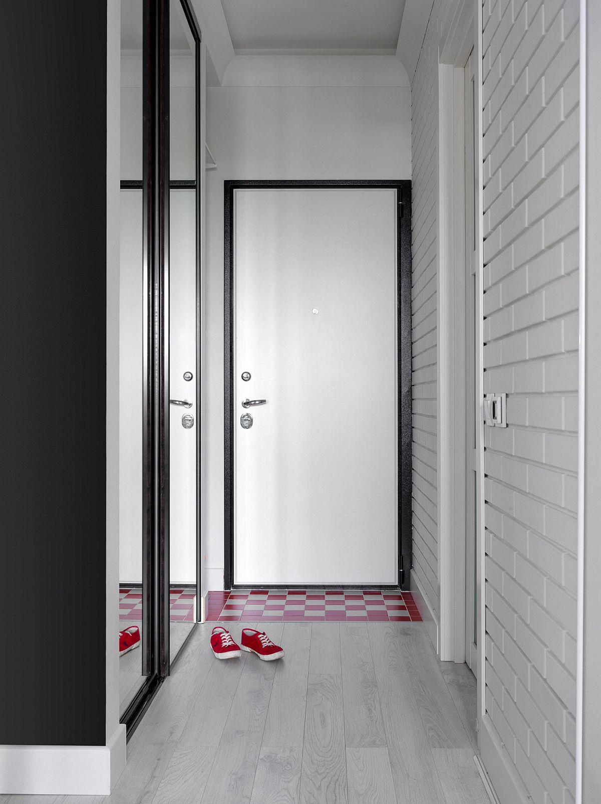 La intrarea în locuință, pe hol, este amplasat un dulap încorporat cu fețele din oglinzi. Finisajul de tip cărămidă nu este unul aplicat, ci este obținut după decopertarea zidurilor și ulterior vopsit totul în alb. Parchetul este montat peste tot în zona de zi și camera copiilor, mai puțin în dreptul ușii de intrare, unde au fost folosite plăci ceramice VitrA montate sub forma unui covoraș.