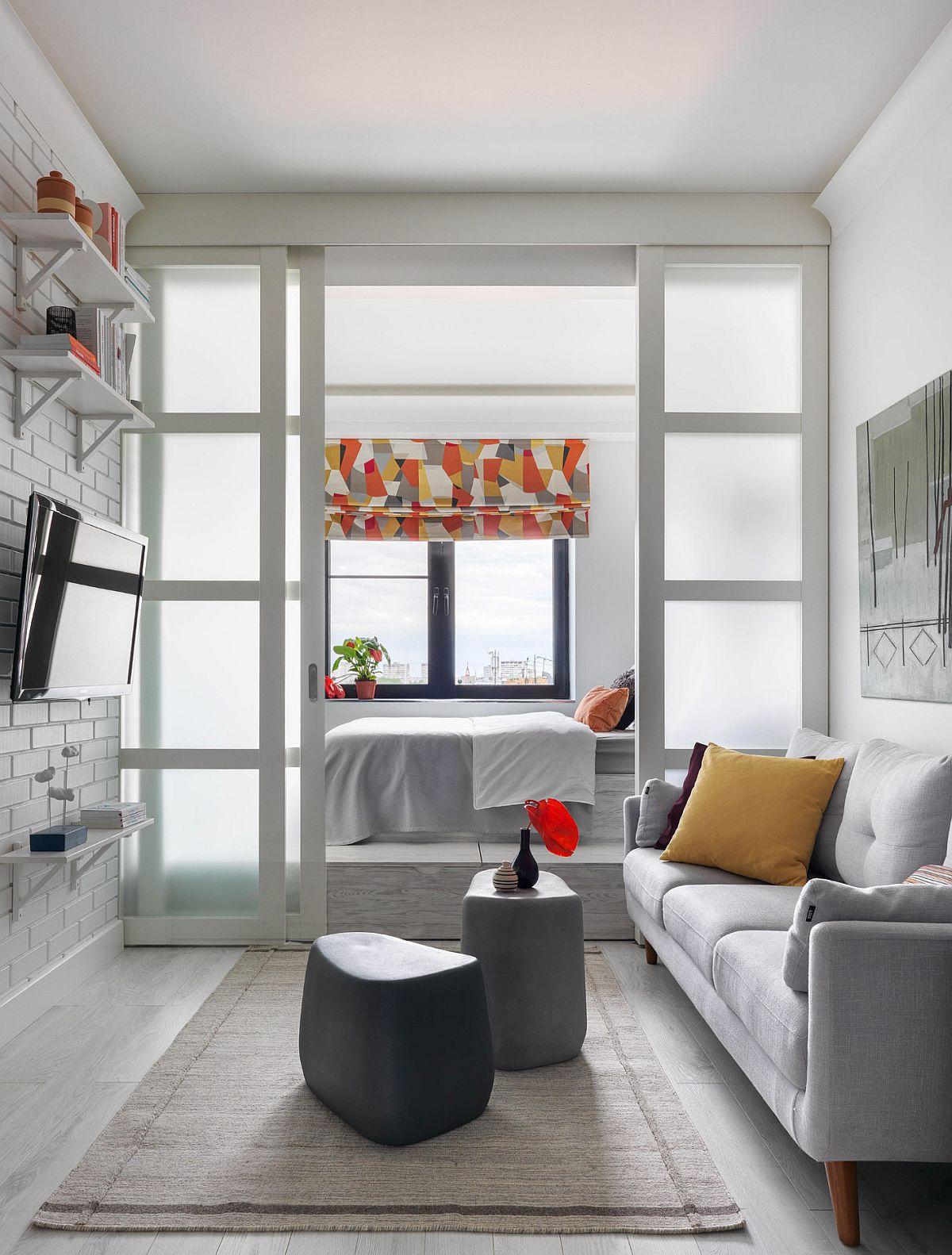 Dormitorul este separat față de living prin intermediul unor uși culisante cu sticlă sablată, realizate pe comandă, care lasă lumina să pătrundă către zona de zi. Un compromis necesar atunci când se doresc mai multe funcțiuni într-o locuință modestă. Spațiul livingului este mic, practic cât lungimea canapelei, dar deschiderea către bucătărie ajută, la fel ca și deschiderea către dormitor.