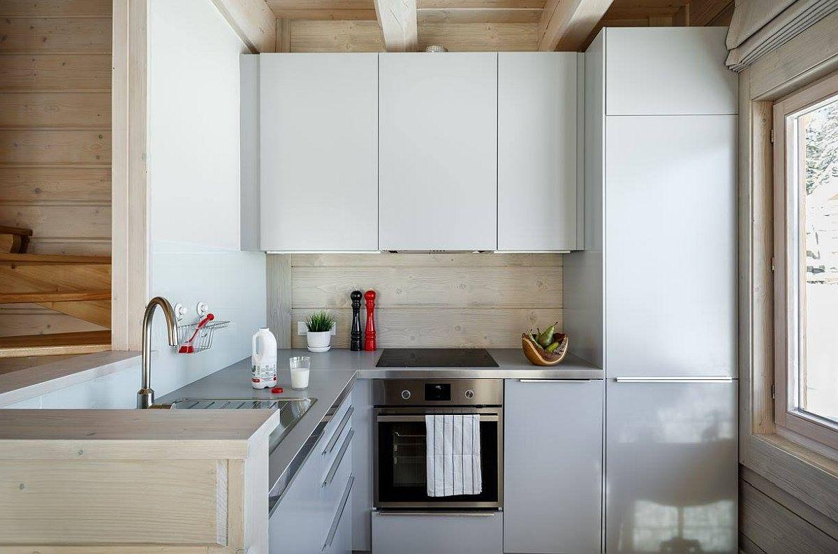 Chiar dacă bucătăria este de mici dimensiuni, dotările sunt corect poziționate,cu spațiu între chiuvetă și plită. Pentru mai multă siguranță, plita este una cu inducție, deci fără flacărăr, așa că finisajul de pe perete a putut fi păstrat din lambriu de lemn. Pentru un aspect contemporan, bucătăria nu are mânere aplicate, iar mobila este într-o singură nuanță, deschisă.