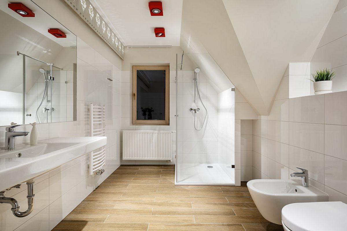 Camera de baie este generoasă, gândită a fi în genul celor matrimoniale, cu două lavoare, având în vedere că este singura baie din apartament. Și ce poți alege pentru un apartament de vacanță? Cel mai sigur este albul pentru finisaje, totul tratat simplu, mininal cu mici accente de culoare la nivelul spoturilor. Albul camuflează volumetria camerei, colțurile de la nivelul plafonului și dă impresia de spațiu mai mare și luminos.