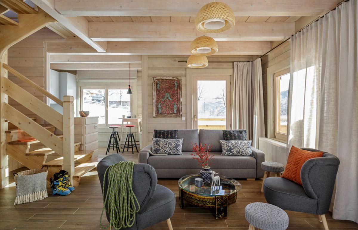 Bucătăria comunică direct cu spațiul zonei de zi, dar este retrasă, având un loc de luat masa u scaune de tip bar. Ferestrele numeroase asigură lumină naturală din plin, iar lambriurile deschise la culoare de la nivelul pereților, precum și structura din lemn de la nivelul plafonului tot în nuanță deschisă face ca ambientul să fie perceput ca prietenos și mult mai generos ca spațiu.