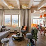 Pe lângă living, zona de zi cuprinde și locul de luat masa, strategic poziționat lângă ferestre. Petele de culoare au fost aduse în sufragerie prin piese mici, începând de la corpurile de iluminat suspendate la scaunele colorate și perne decorative.