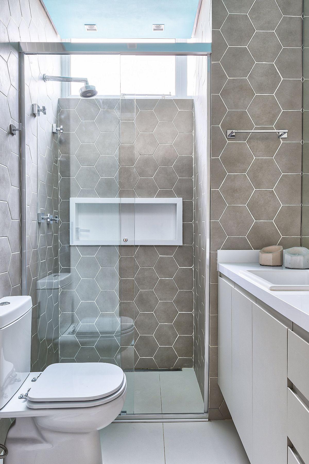 A doua baie din zona de noapte este doată cu duș, unde panoul de sticlă este culisant. Fiind o cameră mică, pereții au fost îmbrăcați cu același tip de gresie hexagonală, iar pardoseala a fost aleasă albă pentru mai multă luminozitate și senzație de spațiu, dar și pentru ca obiectele sanitare și mobila albă să nu fragmente spațiul. Nișa albă din zona dușului este binevenită, dar și vizual conferă armonie în spațiul mic al băii.