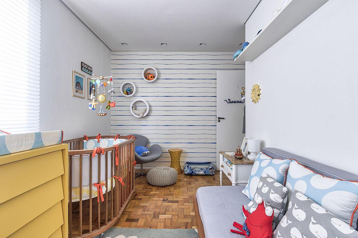 Pentru ca încăperea bebelușui să fie cât mai plăcută, calmă și potrivită și pentru o vârstă școlară, proprietara a ales tema plajei pe care arhitectele au creionat-o cu finisaje simple: pardoseala din lemn veche recondiționată, un tapet deschis cu dungi orizontale care să dea impresia că încăperea este mai lată și un mobilier deschis la culoare, adică piese care ocupă suprafețe mari. Deci totul simplu pentru că într-o cameră de copil întotdeauna jucăriile și accesoriile textile colorează ambientul.