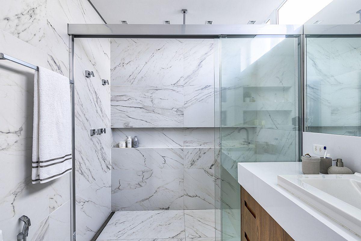 Baia matrimonială este placată cu marmură și are un duș cu rigolă îngropată separat cu uși culisante. Având în vedere că proprietara călătorește mult și vede tot timpul băi în hoteluri de lux, a considerat că varianta cu marmură albă și mobilier cu textură din lemn este rețeta cea mai sigură pentru o baie simplă, dar elegantă.