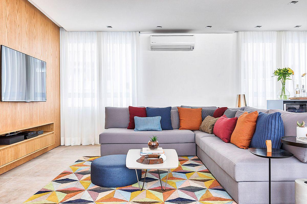 Cum poți aduce culoare într-un ambient tratat cu finisaje simple și o canapea tapițată într-un material de nunață gri? Cu perne colorate, piese mici de tip puf colorate și un covor mai deosebit. Deci nu ai nevoie musai de culori pe pereți pentru a înveseli atmosfera.