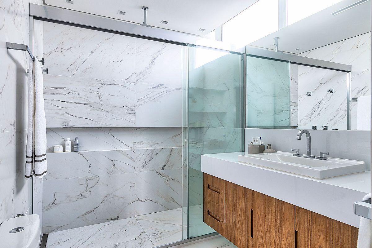 Apartamentul fiind într-o clădire veche, nu avea prevăzut din construcție planșee cu grosimi suficiente pentru ca rigola dușului să fie îngropată la nivelul pardoselii din baie. Ca atare, pentru un duș cu aspect similar pardoseala a fost înaplțată astfel ca rigola cu adâncime de 6.5 cm să poată fi îngropată. De asemenea, separarea zonei de duș este ingenoasă, fiind realizată cu două panouri de sticlă care culisează și al treilea paniu fix. De ce este igenioasă? Pentru că poziția vasului de toaletă și a mobilierului cu lavor nu ar fi permis o închidere cu panouri de sticlă care se deschid similar ușilor.