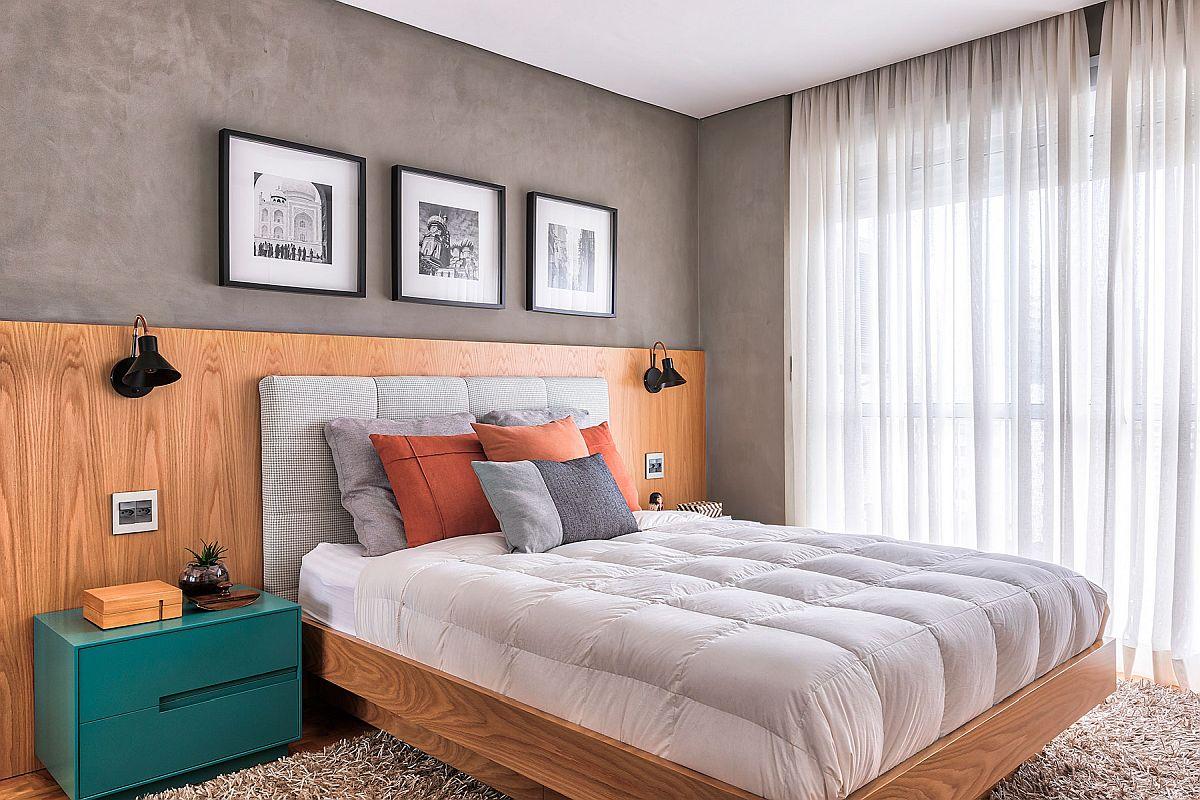 Dormitorul matrimonial este amenajat în ton cu zona de zi. Finisajul gri al pereților îi conferă un aer urban, încplzit de placarea cu textură din lemn ce marchează zona patului. Culoarea? Prin noptiere și perne, dar totul arată ordonat pentru că suprafețele albe sunt semnificative, respectiv la nivelul lenjeriei patului și a țesăturilor ce decorează fereastra.