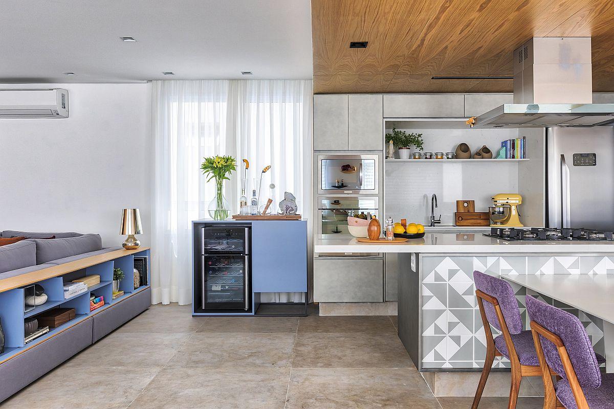 Între bucătărie și zona livingului a fost amplasat frigiderul pentru vinuri. Pentru ca accesul la el să se facă ușor și să nu mai fie înglobat în ansamblul mobilierului de bucătărie, unde ar fi ocupat spațiu necesar depozitării, arhitectele au prevăzut un corp de mobilier special pentru frigider, un corp de mobilier realizat pe comandă. Nuanța albastră a frontului ușii ce ascunde alte sticle și accesorii pentru vin este acceași cu cea de la nivelul bibliotecii amplasată în spatele canapelei.