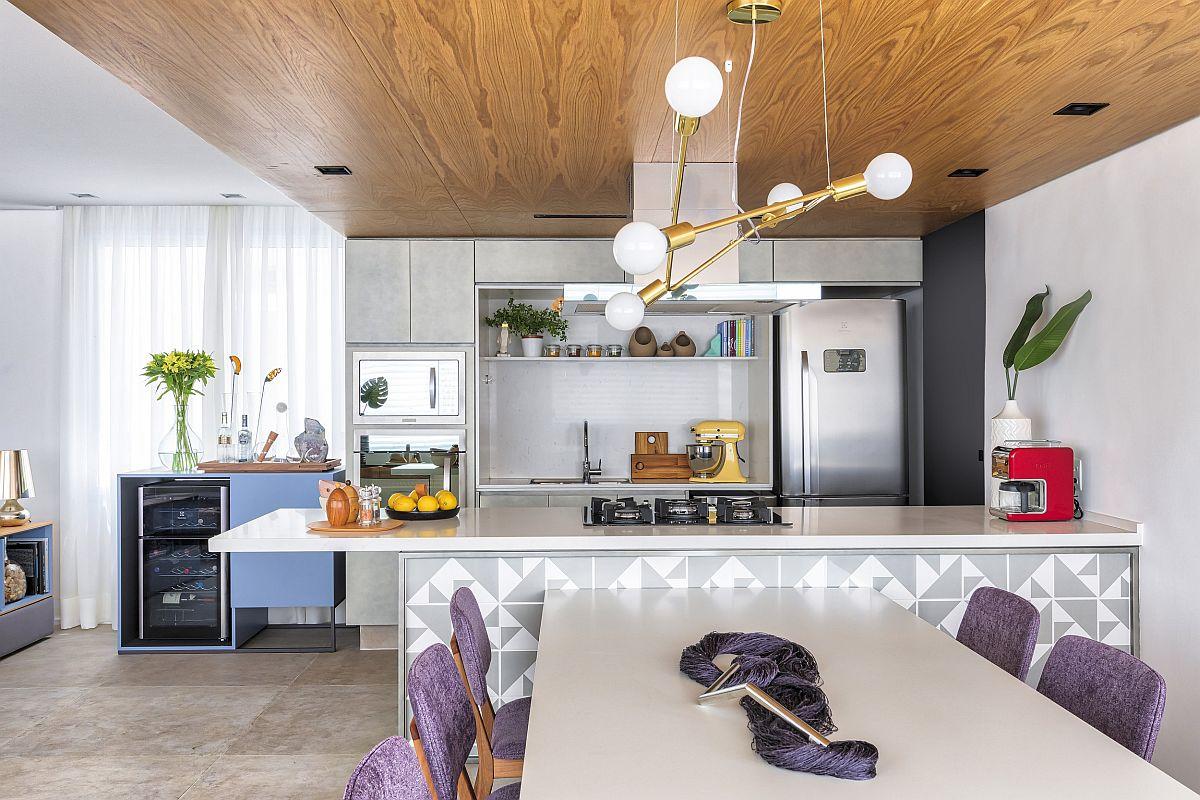 Plăci ceramice cu model geometric îmbracă fața corpului de mobilă de tip insulă din bucătărie. Astfel, chiar dacă la nivelul superior suprafețele sunt tratate simplu, curat, acest detaliu personalizează ambientul, alături de placarea plafonului cu panouri cu textură din lemn (pot fi și PAL) și prezența unui corp de iluminat mai elegant.