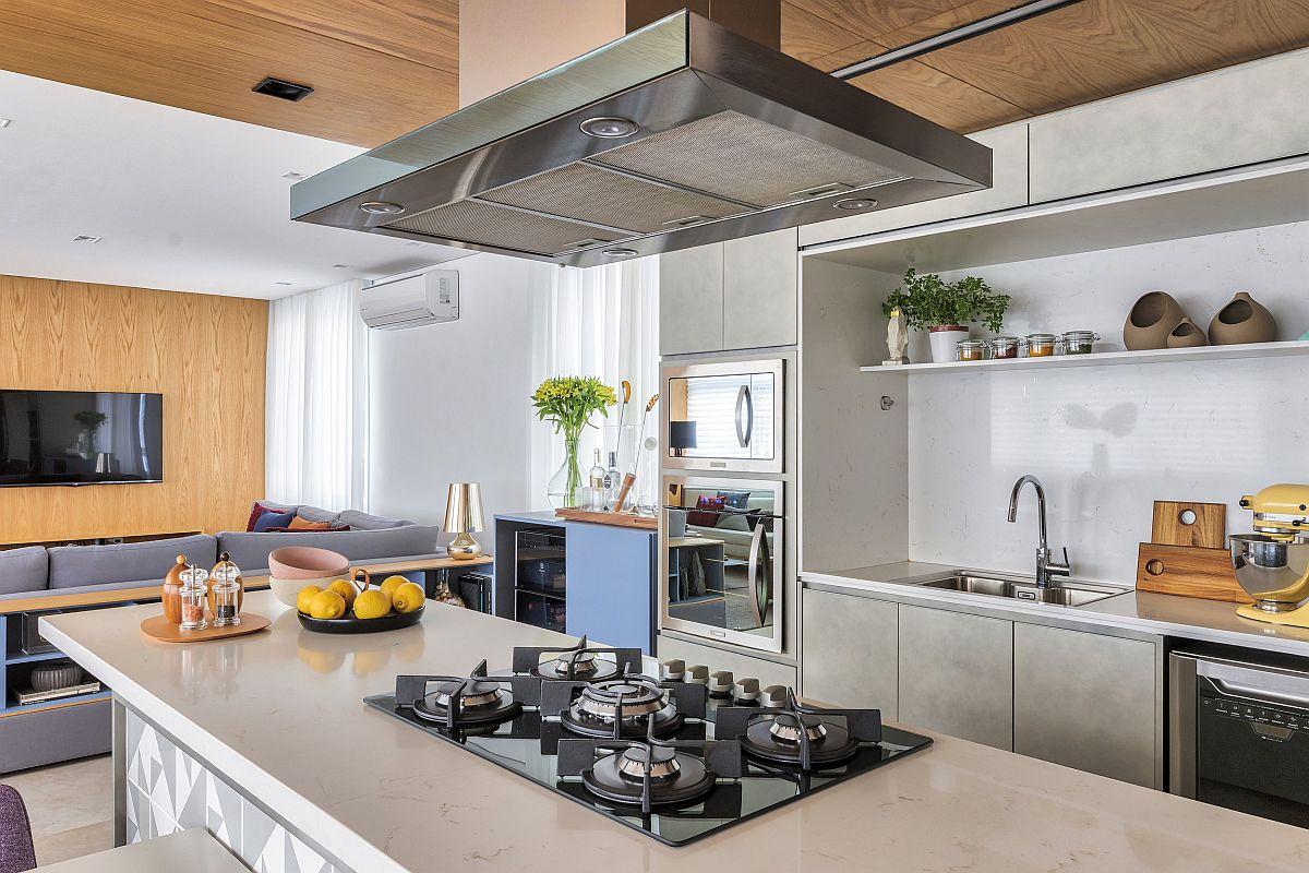 Blaturile de lucru sunt paralele, unul include locul de chiuvetă, iar al doilea, pe masă insulă include locul pentru plită. Prin această poziționare dotările dint bucătărie nu sunt înghesuite, dar și când se gătește, persoana care lucrează în bucătărie nu stă cu privirea orientată doar înspre o latură a bucătăriei, practic cele două blaturi îi permite să interacționeze cu cei aflați înspațiul zonei de zi. Luminozitatea în bucătărie este dată de prezența blaturilor albe, aceeași nuanță fiind și la nivelul mesei încadrată de scaunele cu tapițerie mov.