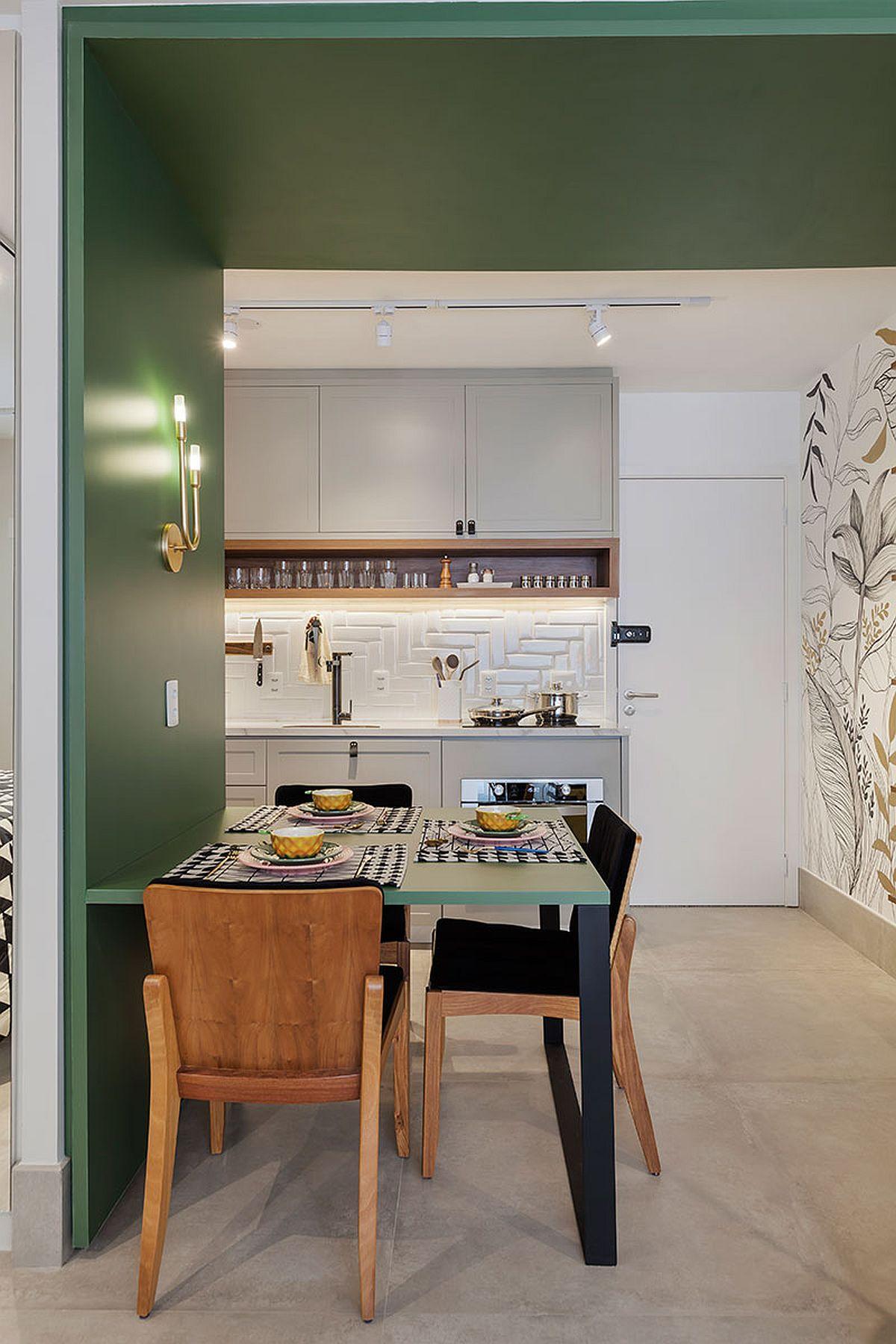 Locul de luat masa este prezent ca funcțiune fixă și este creat între bucătărie și cameră printr-o separare vizuală de efect: placarea cu panouri din MDF vopsite. Această placare este și la nivelul plafonului, ceea ce aduce un plus de culoare dar și separarea vizuală a funcțiunilor.