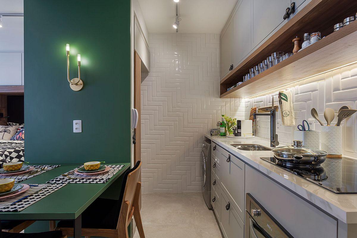 Între bucătărie și dormitor s-a făcut o separare cu mobilier. Pe o parte, către bucătărie e loc pentru frigider și spații de depozitare, iar către cameră loc de dulapuri. Locul mașinii de spălat este în bucătărie, ca atare tot peretele din zonă a fost placat cu faianță de tip Metro, dar montată diferit față de cum ai văzut până acum. Pentru că bucătăria este într-un spațiu fără fereastră, iluminatul a fost gândit atât local, deasupra baltului, cât și general, la nivelul plafonului.