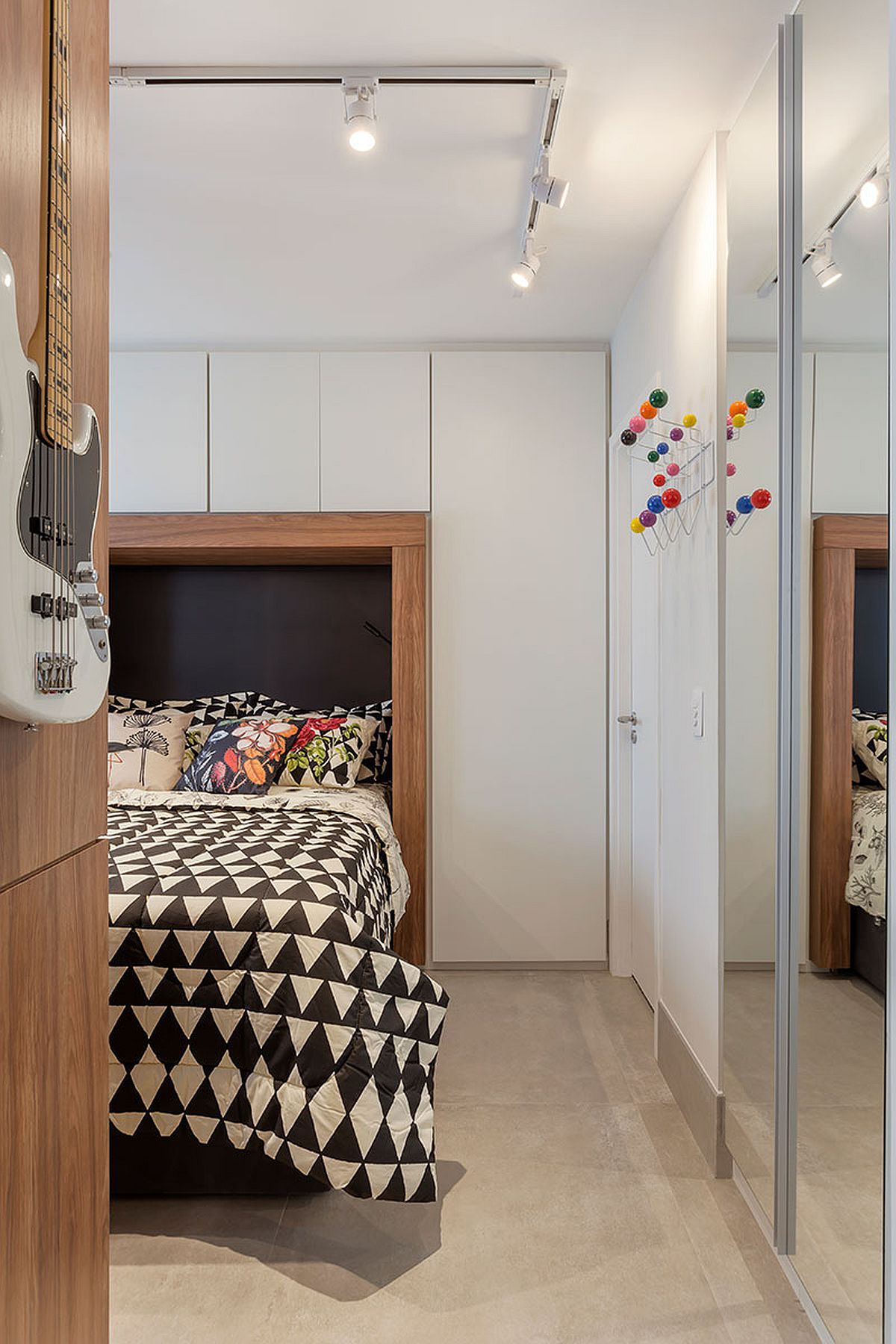 Iluminatul general, adică cel de la nivelul plafonului, este peste tot cu șine cu spoturi, la fel ca și finisajul pardoselii cu plăci mari de gresie în nuanța gri, similară betonului. La intrarea în spațiul dormitorului nu există ușă pentru că în lateral, pe aceeași parte cu accesul către baie este configurat un spațiu de cuier, deci unde e nevoie să se ajungă ușor.