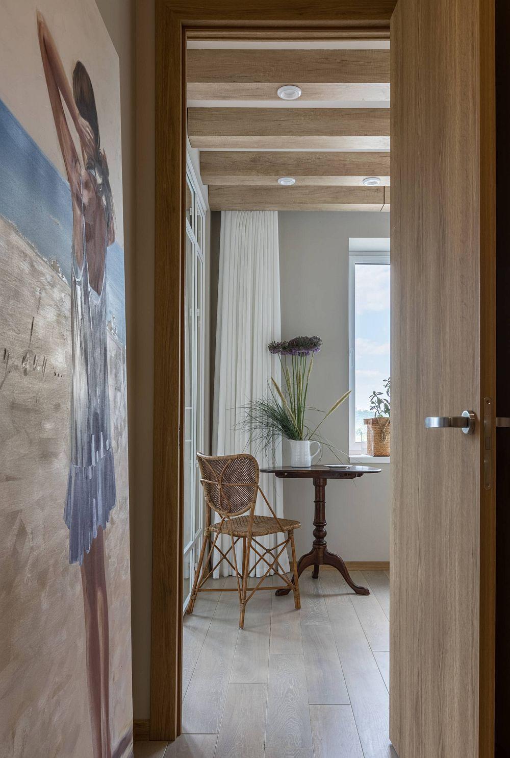 În holul de la intrare, după dulapurile încastrate, peretele a fost folosit pentru poziționarea unui tablou de dimeniuni mari, tablou care vorbește despre tema aleasă de către proprietară - ideea de casă de vacanță. Astfel și când ușa bucătăriei este deschisă, tabloul se vede frumos din zona locului de luat masa, nu doar la intrarea în casă.