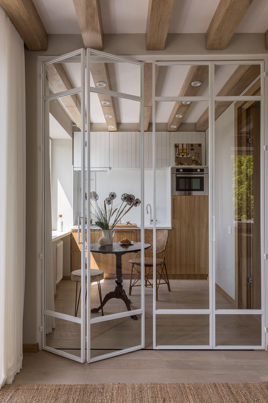 Între bucătărie și cameră au fost prevăzute uși de tip armonică cu tâmplărie metalică vopsită în alb și geamuri mari.