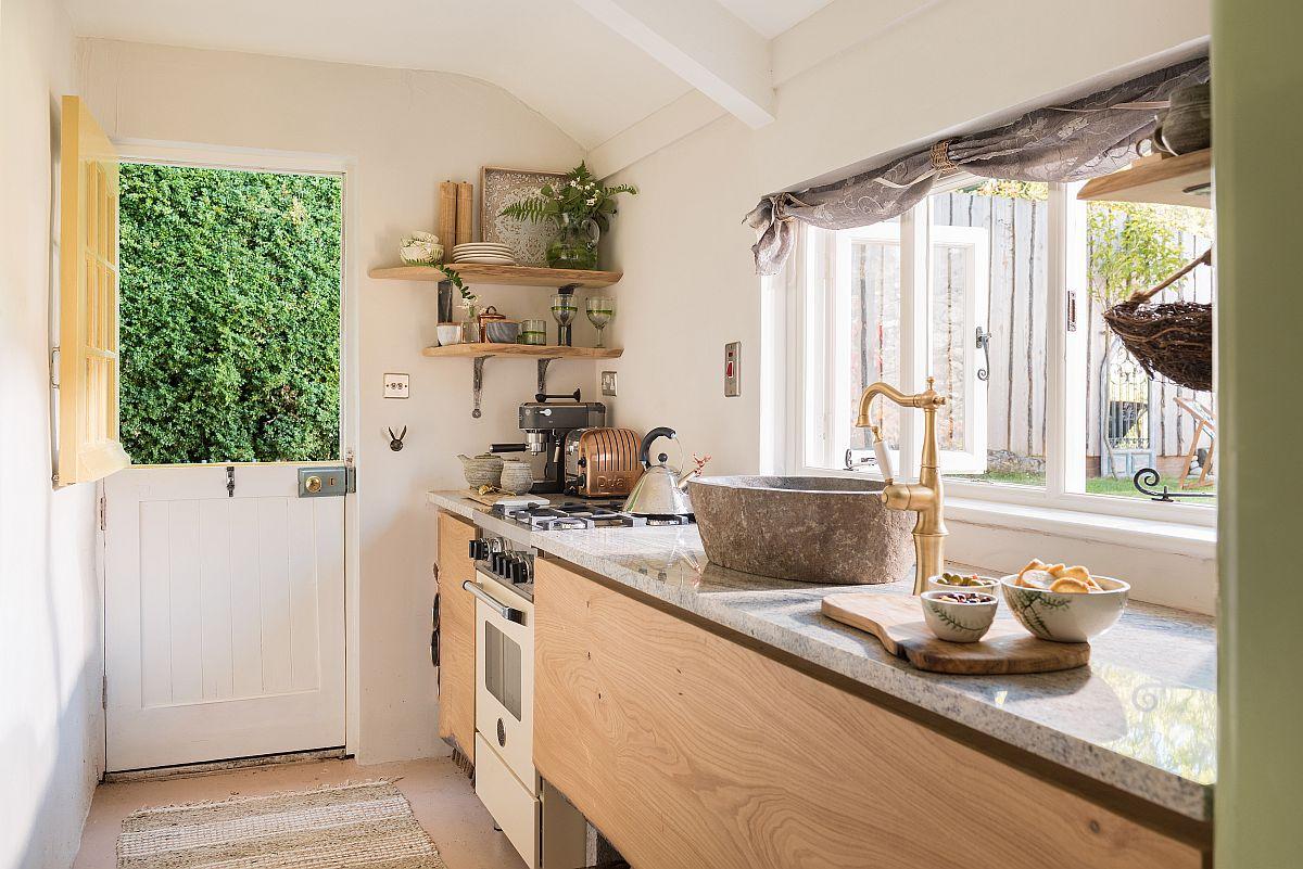 Bucătăria, un spațiu îngust și lung, est eun spațiu luminat natural din plin, ceea ce o transformă într-o încăpere primitoare. Fereastra mare dă înspre grădină, amenajată frumos și ea pentru relaxare. Dotările sunt actuale, dar proprietarii au ales electrocasnice cu design retro.