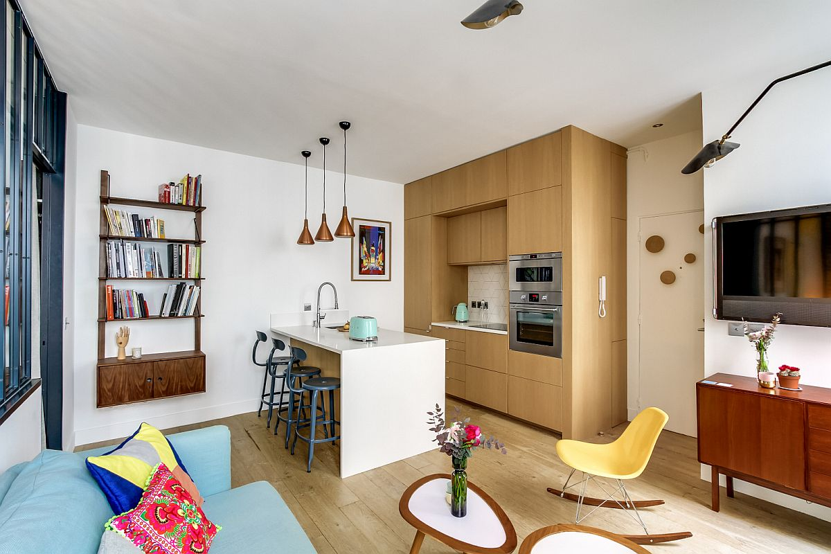 Comoda retro de sub televizor are un corespondet ca stil în etajera suspendată din spatele scaunelor de tip bar. De reamarcat faptul că bucătăria este de fapt foarte aerisită, având în vedere că deasupra mesei insulă nu există nimic aglomerat, fără corpuri de mobilier sau obiecte masive. De aici și senzația de spațiu mai mare.