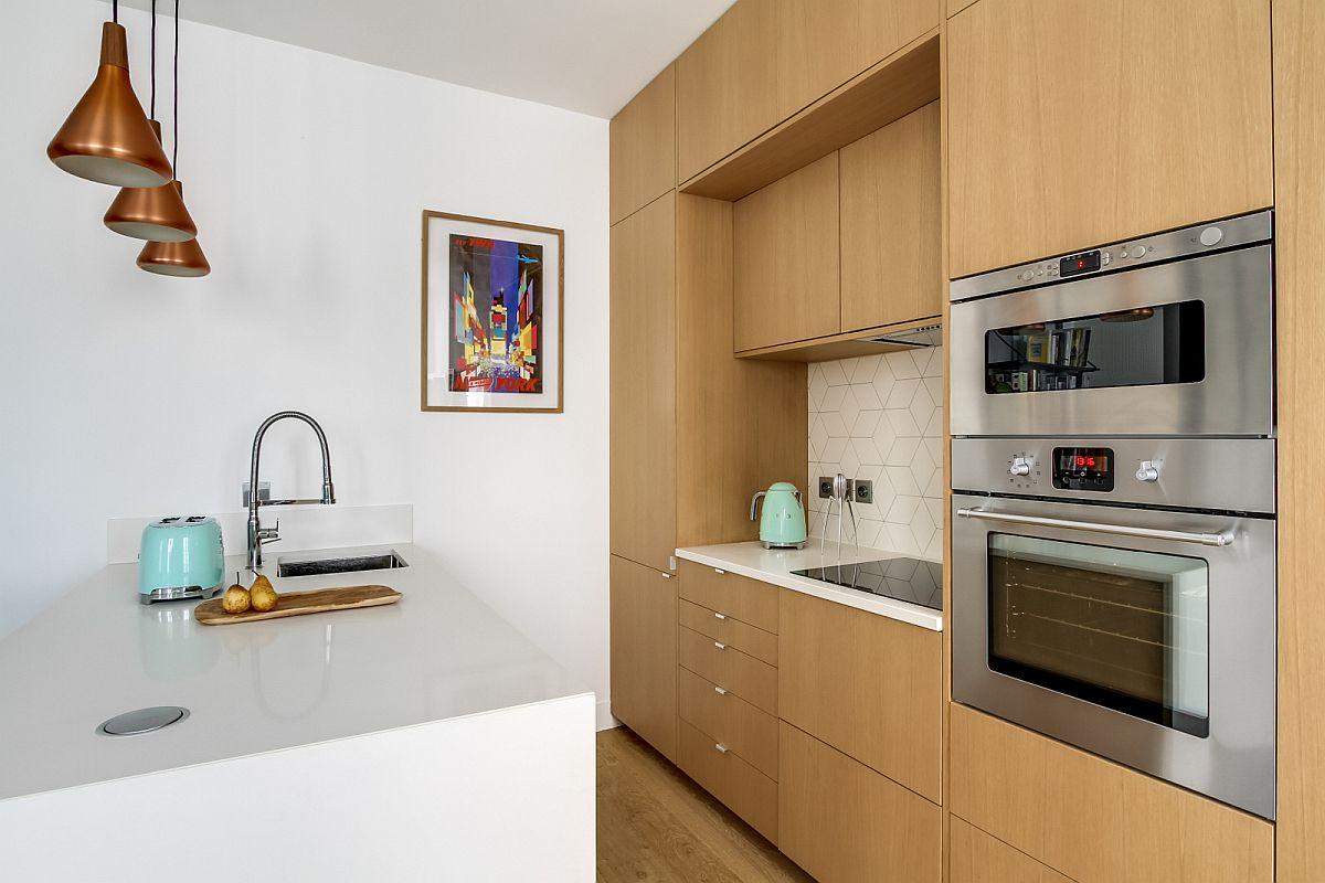 Mobila de bucătărie este configurată pe perete până în plafon și are partea de plită pe blat, combina frigorifică fiind încorporată. Pentru depozitare mai eficientă au fost prevăzute sertare în locul ușilor de dulap, asta sub blatul din cuarț alb. Partea de sus a corpurilor suspendate maschează tubulatura pentru hotă, dar și alte trasele. O parte din spațiu poate fi folosit pentru depozitarea unor lucruri care sunt folosite mai rar.