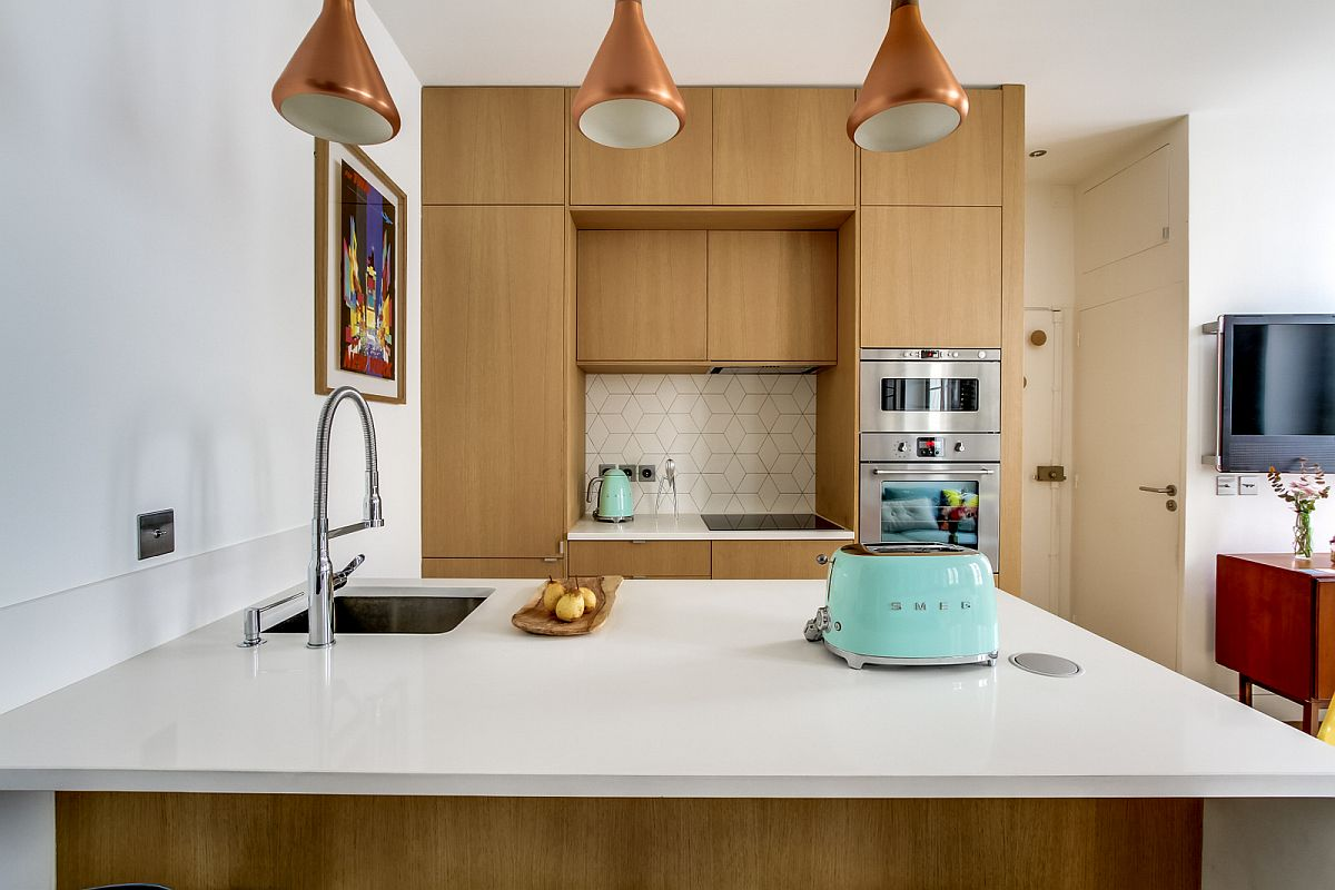 Pentru a completa bucătăria, designerii au prevăzut o masă pensinsulă în care este încastrată chiuveta. A fost aleasă o chiuvetă sub blatul de cuarț alb. Sub blat pe partea către cameră sunt sertare, iar sub chiuvetă sunt uși de dulap.