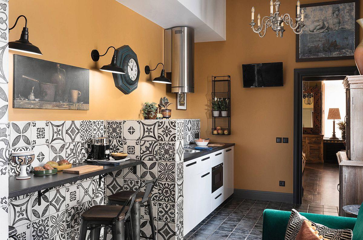 Între locul de luat masa și bucătărie există un zid parțial, care lasă la vedere zona superioară a locului de gătit. Folosind o nuanță solară pentru pereți, un portocaliu cald, spațiul pare mai lat și mai luminos. Dar pentru asta, partea de sus a bucătăriei nu este aglomerată cu corpuri de mobilă suspendate, designerul a prevăzut în schimb obiecte decorative, dare distrag atenția de la mcul ecran tv și care continuă frumos abordarea artistică.