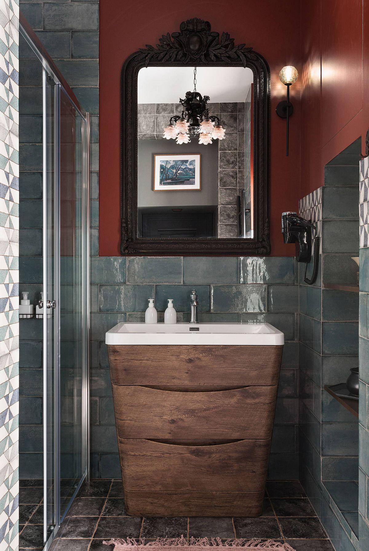 Lavoarul este frumos înglobat într-un mobilier furniruit, iar zona este suprinzător accentuată cu o oglindă cu ramă veche, bogat ornamentată. O combinație inedită de stiluri, care transformă total percepția asupra camerei de baie.