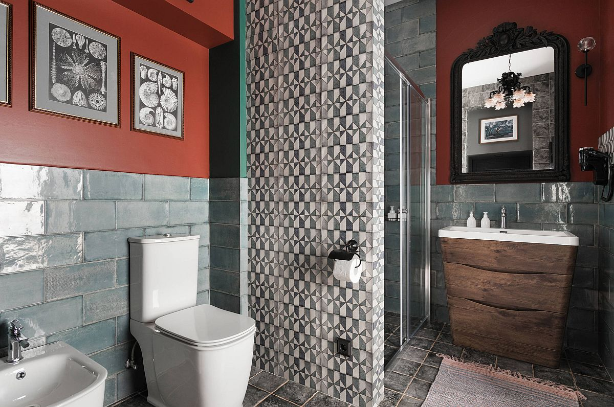 Camera de baie este surprinzătoare. Designerul s-a folosit de spațiul existent pentru a delimita zona de duș față de vasul de toaletă și bideu. Plăcile ceramice sunt frumos combinate aici, nu doar ca model și culoare, ci și ca textură. Dacă pentru pereți și duș s-au folosit plăci ceramice lucioase, pentru peretele despărțitor s-au ales plăci cu aspect mat, care par să continue finisajul de la nivelul pardoselii.