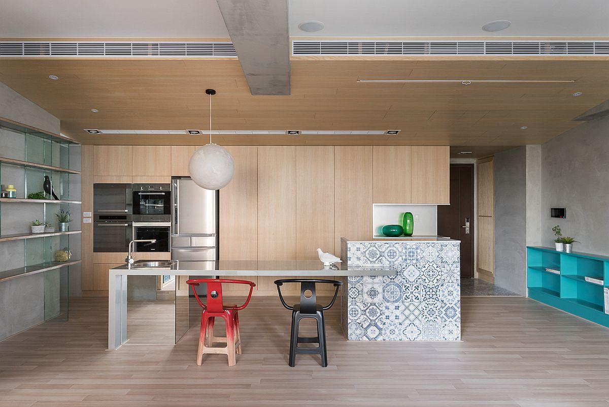 Bucătăria este primul spațiu imediat de la intrarea în apartament. Lângă ușa de intrare eistă un mic loc de cuier, dar închis. Arhitecții au prevăzut ca plafonul din zona bucătăriei și sufrageriei să fie placat cu același material ca pentru mobila din bucătărie. Astfel, chiar dacă încăperiile comunică deschis, ele sunt tratate diferit ca finisaje la nivelul pereților și plafoanelor. Tavanul fals din bucătărie include și sistemul de ventilație și maschează traseul instalațiilor.