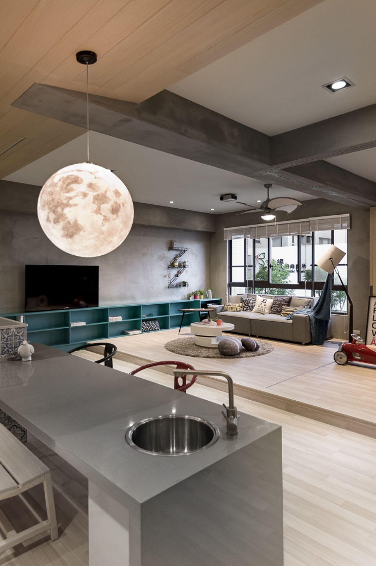 Deasupra mesei insulă, care include o chiuvetă mică, este o suspensie, un corp de iluminat care imită aspectul Lunii. Un accent ludic, care completează ideea de spațiu de joacă al acestui spațiu generos.