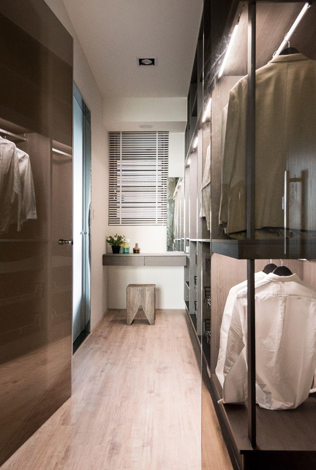 În dressingul părinților este prezentă și o mică masă de toaletă, poziționată în fața micii ferestre prezente aici. Dulapruiel sunt configurate deschis, fără uși, dar dressingul este separat de cameră prin panouri de sticlă fumurie.