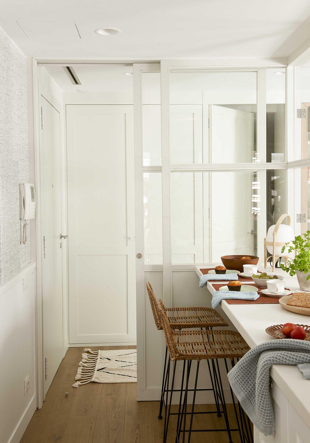 Intrarea în locuință coincidea inițial cu intrarea în zona de zi, care era un open space, cu bucătărie deschisă către living. Designerul a avut însă în vedere în primul rând crearea unui spațiu de depozitare cu rol de cuier, realizat sub forma unor dulapuri albe pe comandă, care aproape că nici nu se văd pe fundalul alb al pereților. Apoi, a delimitat bucătăria cu tâmplărie, bucătărie putând fi închisă cu ușă culisantă.