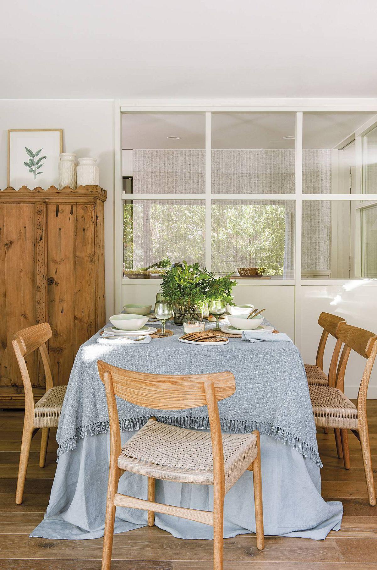 De partea cealaltă a tâmplăriei ce separă locul de luat masa din bucătărie, în living a fost așezată masa de sufragerie. O continuare logică, dar și funcțională pentru un spațiu în care s-au dorit foarte multe piese de mobilier. Accentele rustice sunt evidente la nivelul mobilierului, dar pentru a mai atenua caracterul rustic, masa a fost îmbrăcată cu o față de masă prin care se aduce un strop de culoare la interior.