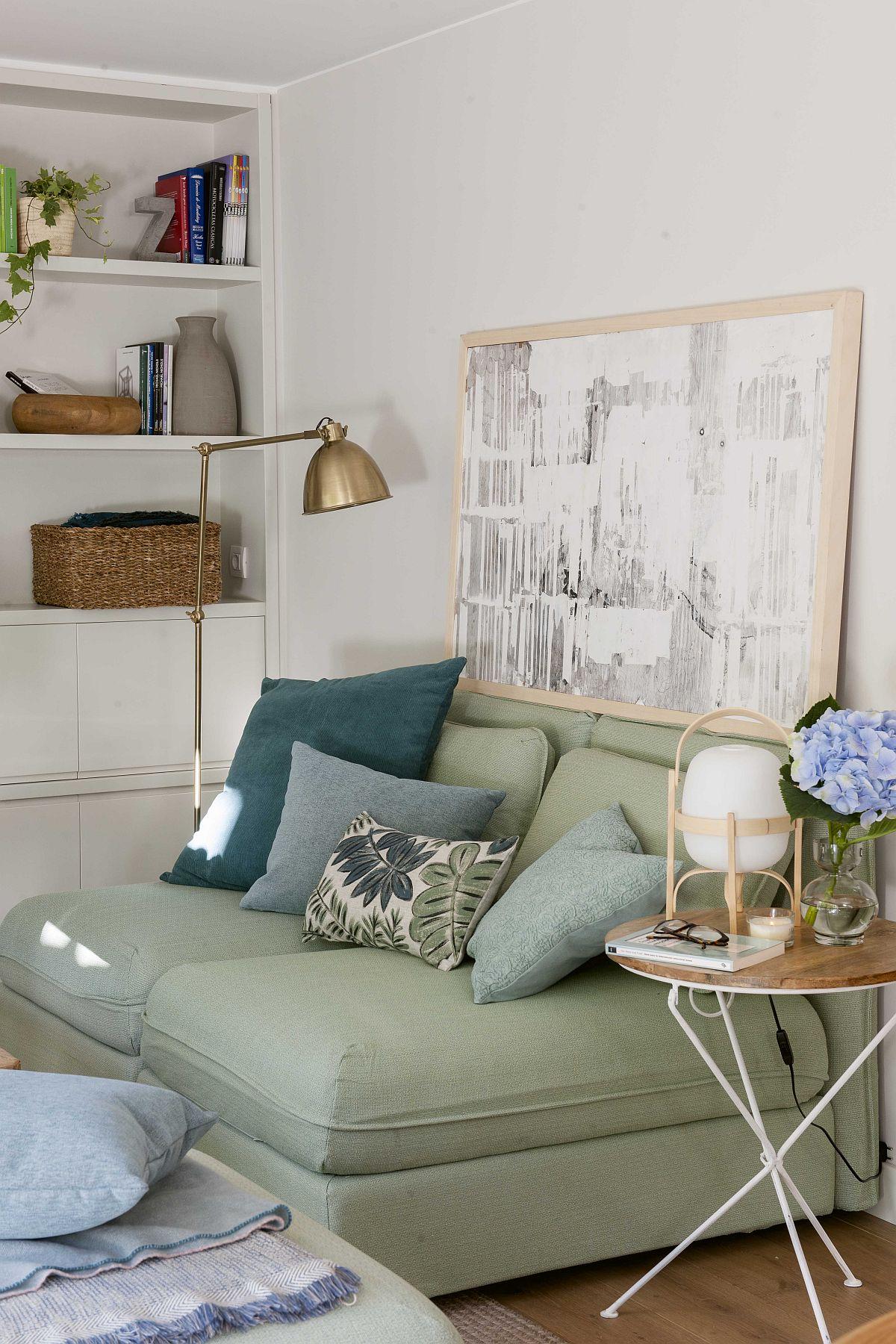 Accentele rustice sunt prezente și în zona canapelei, chiar dacă mult mai discret: măsuțele cu blat din lemn, rama din lemn a tabloului, coșurile împletite din bibliotecă. Un lampadar a fost ales pentru iluminare artificială punctată, binevenit mai ales pe timp de seară.