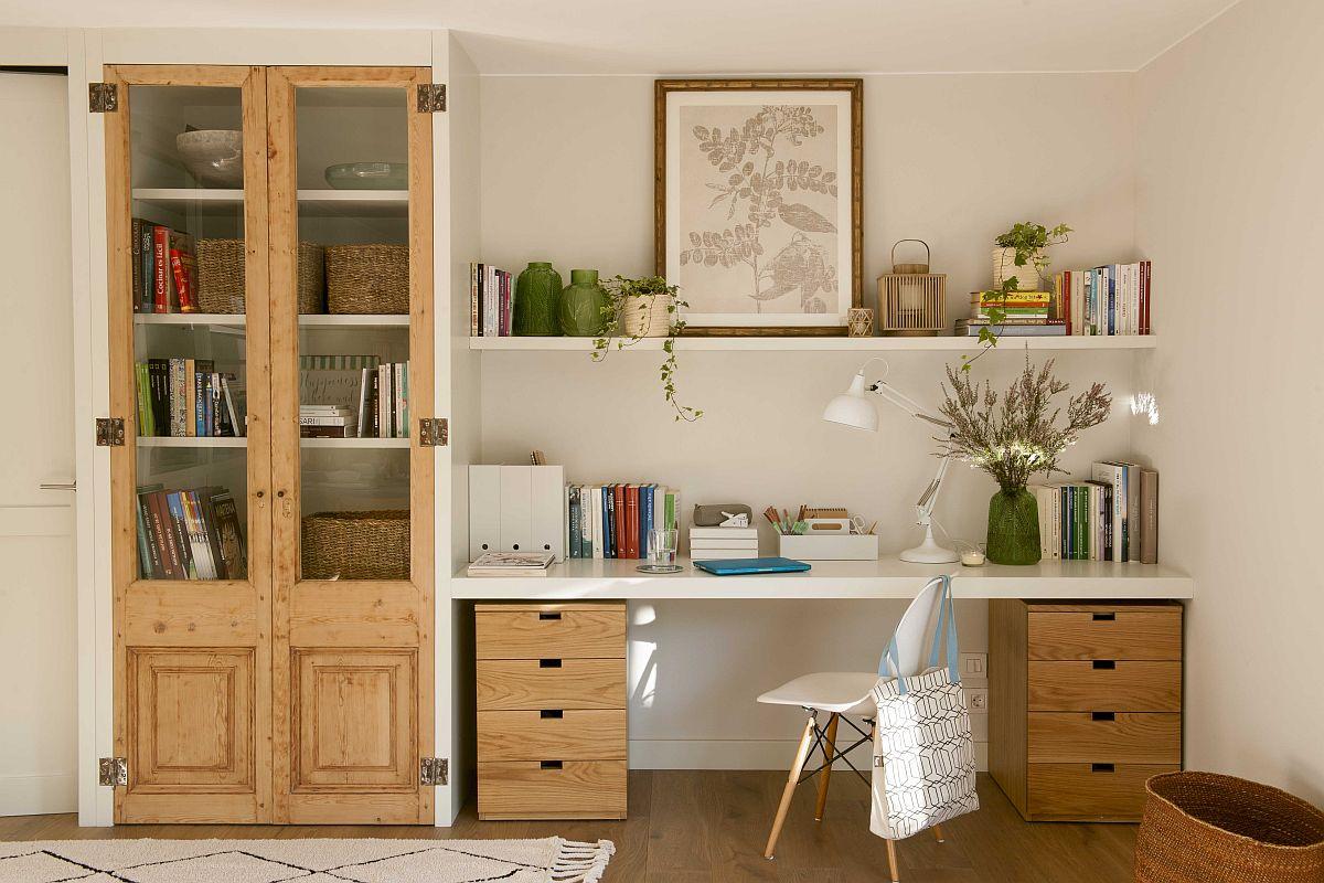 Zona de birou este excelent gândită de către designer. Dulapul cu vitrină are partea inferioară fără geamuri pentru vesela de ocazie, iar în vitrină sunt cărți. Dar tot în partea de jos sunt și corpurile cu sertare cu textură lemn ales biroului. Laterala dulapului delimitează zona de birou, dar oferă suport pentru prinderea raftului și blatului de lucru. Detalii pentru balamamele de prindere și textura lemnului te duc cu gîndul la rustic, chiar dacă carcasa și blaturile sunt din registrul actual.
