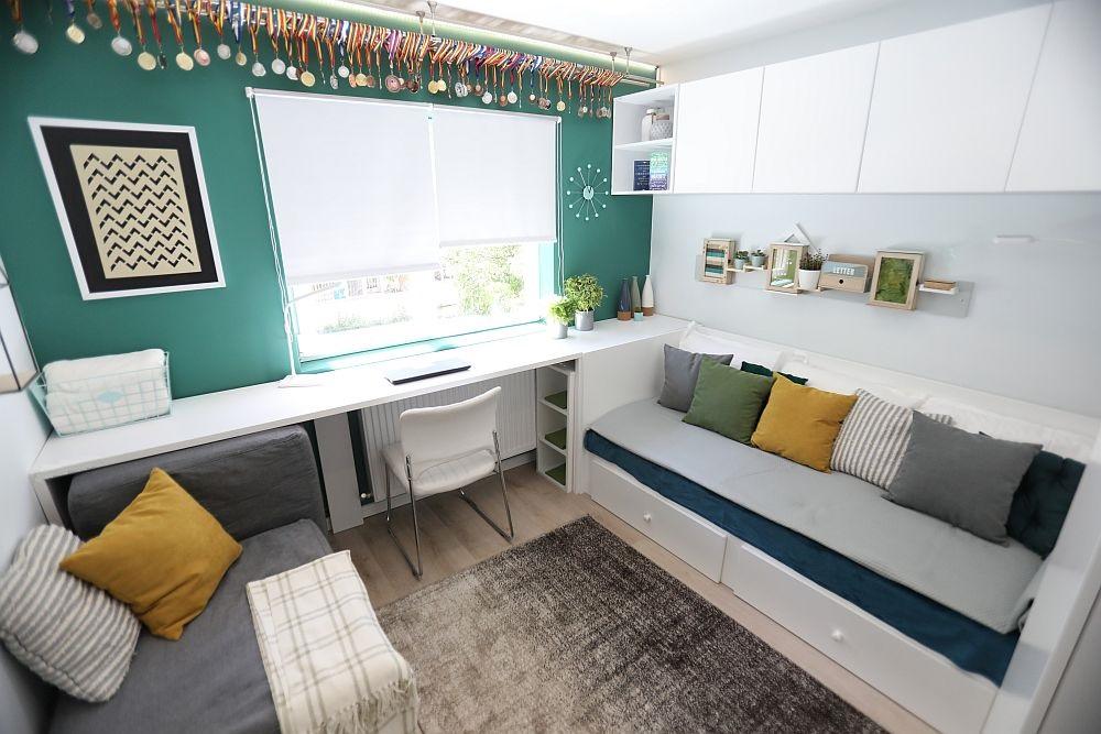 Cameră pentru un copil adolescent, cu biroul poziționat în fața ferestrei și patul pe lățimea camerei.