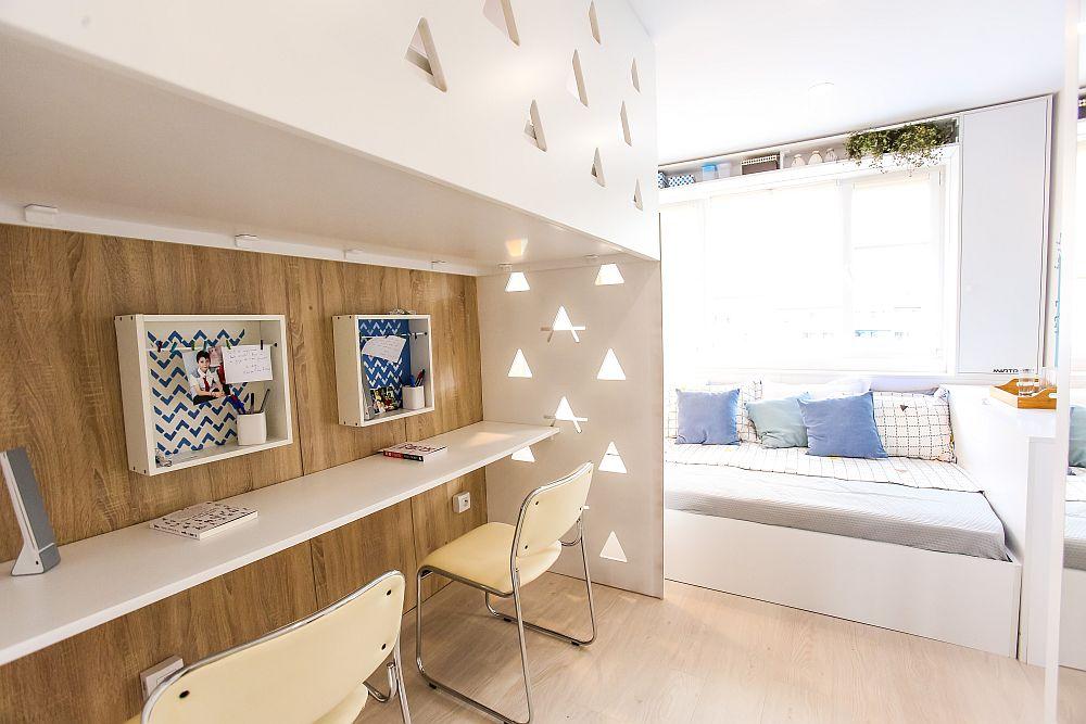 Cameră de bloc pentru trei frați, unde doi dintre ei de vârstă școalară împart un pat pus în fața ferestrei și locul de birou configurat sub patul etaj (corespondent celui de-al treilea frate).