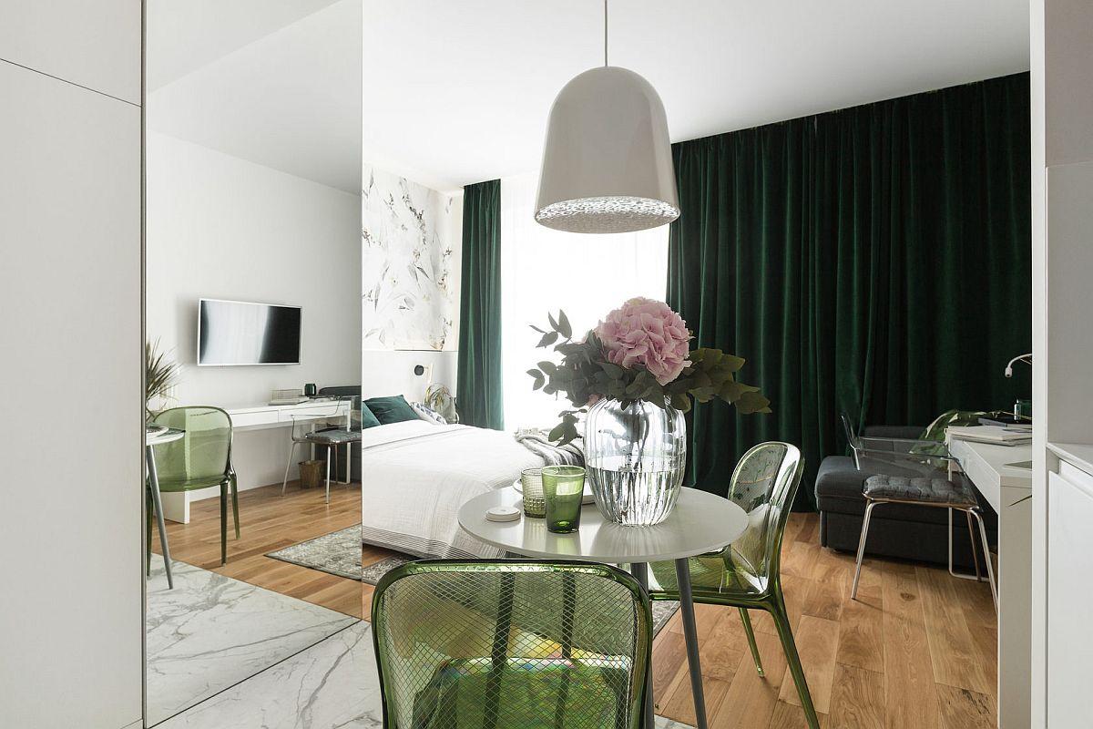 Finisajele alese pentru garsonieră sunt simple, dar elegante. Alb cald pentru zugrăveala pereților, plăci ceramice cu muchii rectificate și aspect de marmură în zona de bucătărie și baie, parchet pentru cameră. Pe fundalul alb al pereților și tavanului, arhitectul a prevăzut pete de culoare prin draperia grea de catifea, tapițeria fotoliului extensibil, nuanța scaunelor și culoarea pentru ușa de intrare. S-a folosit și de oglinzi pentru a da impresia de spațiu mai mare, iar corpurile suspendate nu există pe centrul spațiului, ci sunt poziționate local (deasupra mesei și în lateralul patului).