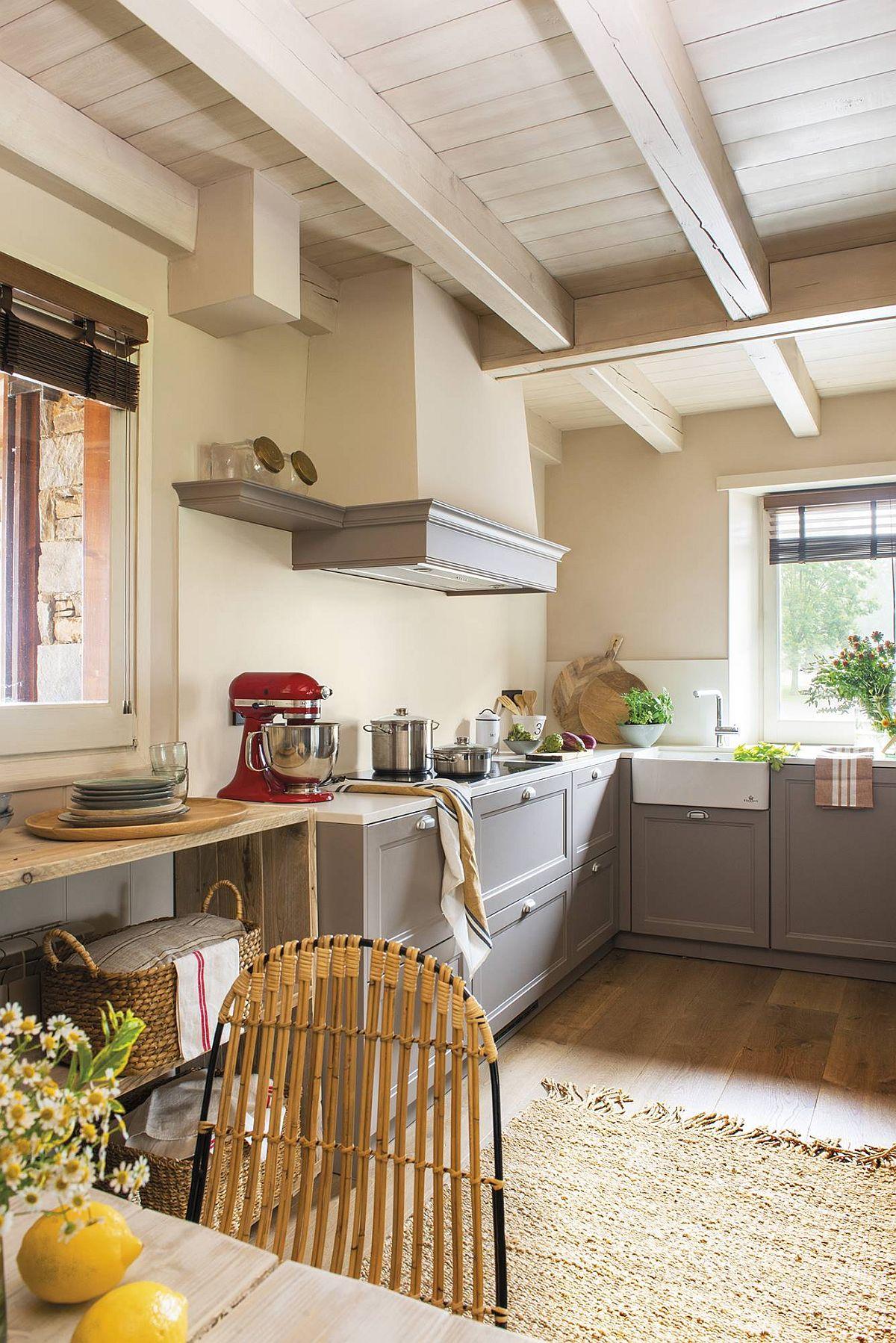 Fostul hol al casei a fost adaptat pentru bucătărie, gîndită fără corpuri suspendate din cauza prezenței ferestrelor. Ca atare, arhitecții au prevăzut o hotă decorativă care să marcheze aerul rustic. Partea modernă survine la nivelul blatului și placării pereților cu același material compozit pentru a crea suprafețe simple, curate, ordonate.