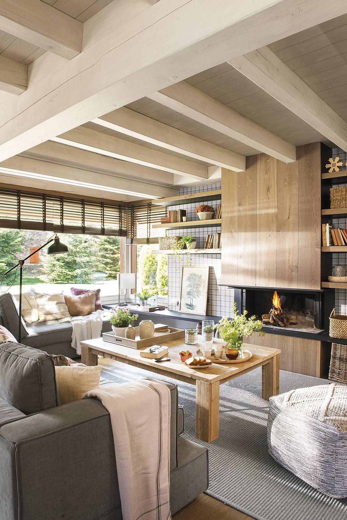 În același spațiu cu sufragerie este și locul de conversație marcat prin poziționarea mobilierului. Practic doar prin așezarea canapelelor s-a demarcat livingul, fără alte separări. Dar și livingul beneficiază de o fereastră generoasă, ceea ce contribuie la atmosfera generală a casei. Dacă în sufragerie s-au prevăzut draperii, fără perdele, mai departe în living au fost prevăzute jaluzele orizontale din lemn. Fiind în același spațiu cele două zone, țesăturile draperiilor se simt în ambientul parterului, dar ele ar fi incomodat în living unde una dintre canapele este cu spatele la fereastră. De remarcat tapițeria gri pentru canapele, o culoare care se asortează ușor cu orice altă nuanță, dar care rezistă și la murdărire, mai ales că în această casă sunt trei copii de vârstă școlară.