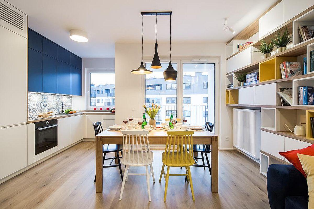 Intrarea în locuință coincide cu cea în spațiul zonei de zi, unde bucătăria, sufrageria și livingul coexistă. Tinerii proprietari și-au dorit o masă generoasă, ca atare bucătăria a fost lăsată deschisă pentru ca spațiul pentru sufragerie să poată fi ușor configurat. Ceea ce i-a ajutat pe designeri a fost faptul că proprietarii nu și-au dorit televizor în living, ei urmărind programe sau filme pe Internet.
