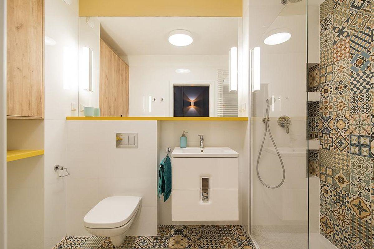 Baia este amenajată funcțional și colorat cu mobila încastrată în nișa de aici. Dușul s-a dorit mai spațios, ca atare lavoarul ales este unul de mici dimensiuni. Oglinda supradimensionată dă senzația de spațiu mai mare și mai luminos.Suprafețe albe sunt prezente exact unde sunt și obiectele sanitare (vas de toaletă și lavoar) tocmai pentru a estompa prezența acestora.