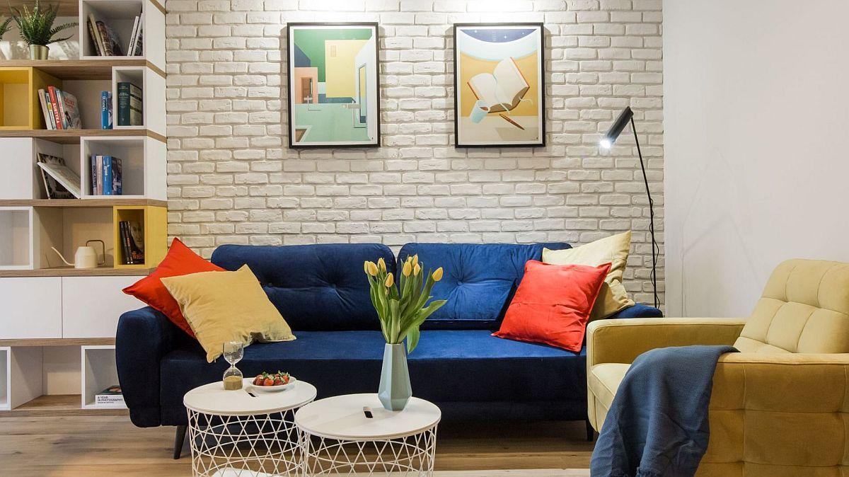 Deși pereții sunt albi și pardoseala aceeași în toată zona de zi, prin tapițeriile pieselor de mobilier s-a adus culoare în zona de ședere. Contrastul de albastru și galben dintre canapea și fotoliu este potențat și de pernele de culoare roșie. Posterele înrămate de deasupra canapelei sunt alese în ton cu amenajarea, atât ca temă, cât și ca mesaj.