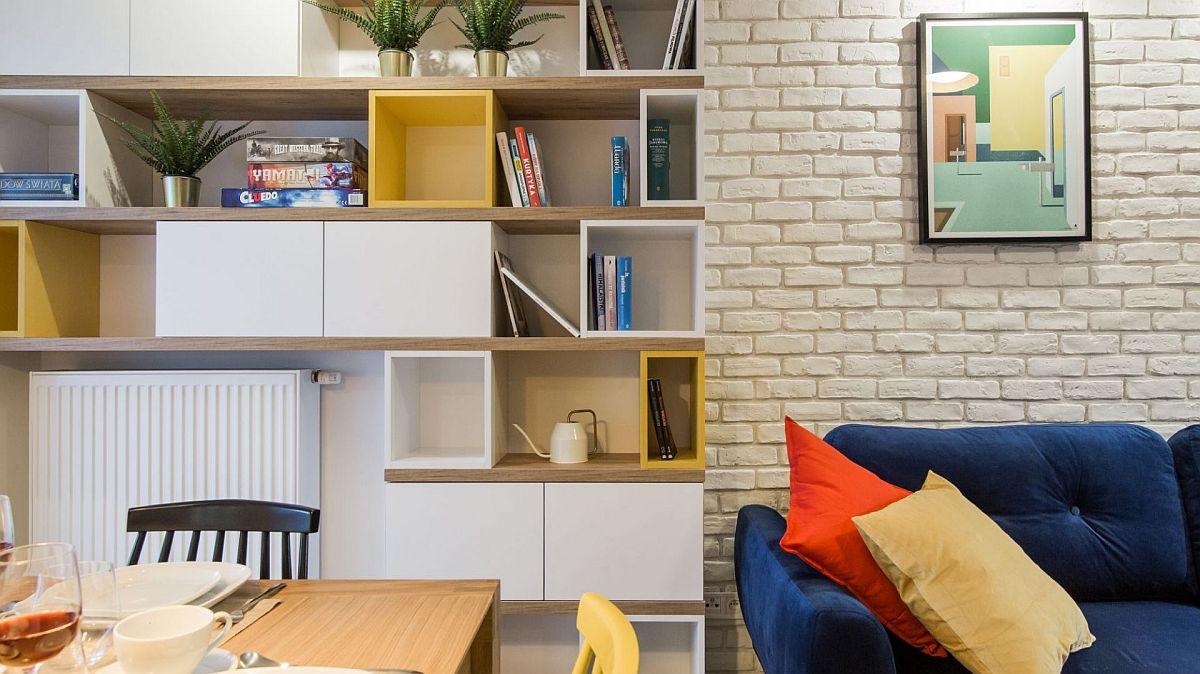 Pentru ca spațiul să nu fie încărcat, dar și suficient colorat, designerii au prevăzut biblioteca cu materiale în nuanță albă (ca și dulapurile din bucătărie), textură lemn (similară mesei și blatului din bucătărie) și câteva elemente galbene (care aduc senzația de soare și strălucire).