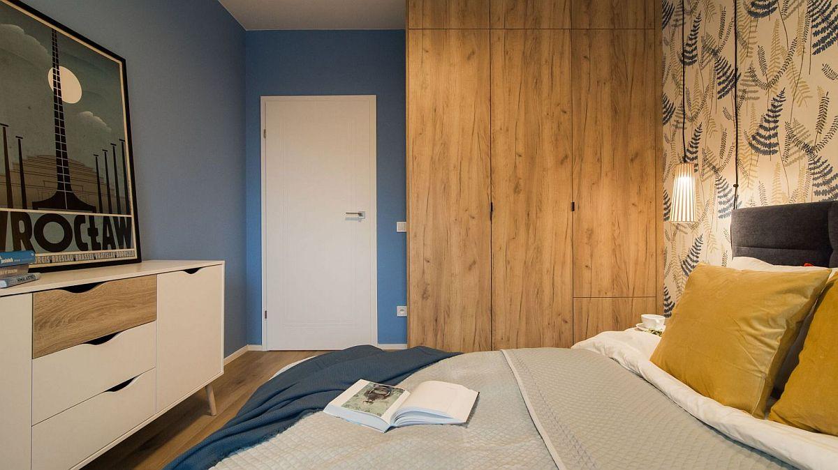 Atât peretele cu ușa, cât și cel din fața patului sunt într-o nuanță închisă de albastru, ceea ce face ca încăperea să se simtă mai intimă, dar tot ce e în jurul ferestrei e lăsat alb pentru un plus de luminozitate.