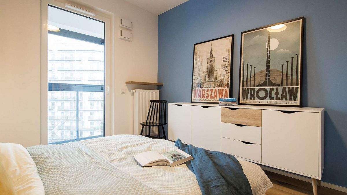 În fața patului o comodă cu sertare completează necesarul pentru depozitarea hainelor. Contrast de alb-albastru care te duce cu gîndul la ideea de vacanțe la mare și două postere decorează exact cât trebuie zona.