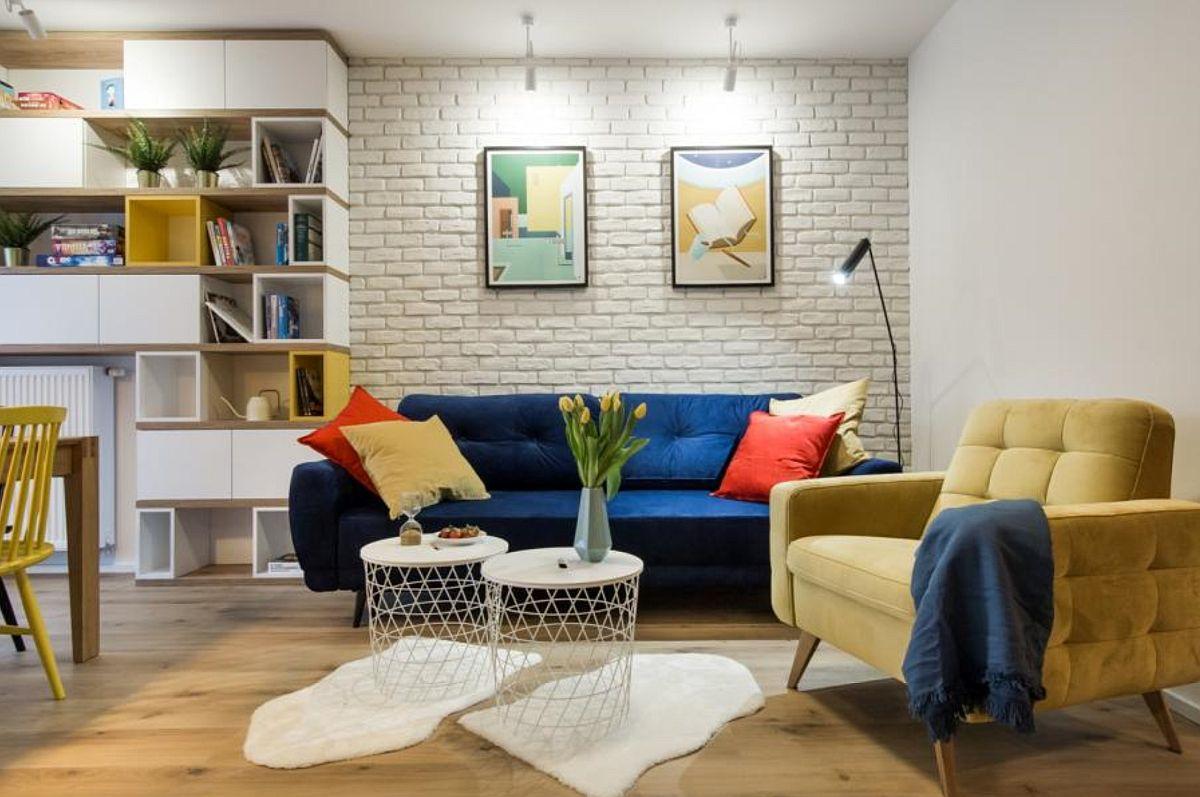 Pentru un plus de textură, peretele din spatele canapelei este îmbrăcat cu cărămidă aparentă. Zona este bine pusă în evidență și prin iluminat punctat.