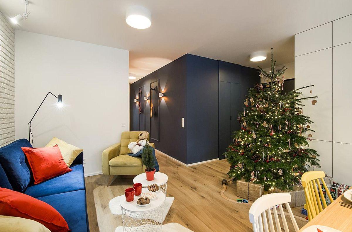 Designerii au luat în calcul în amenajarea locuinței și locul de brad pe timpul iernii, gândit chiar la zona de intrare în locuință. În imagine se vede locul de acces în apartament, dar și holul către zona de noapte, unde pereții sunt vopsiți într-o nuanță închisă de albastru, care dă senzația de adâncime a spațiului.
