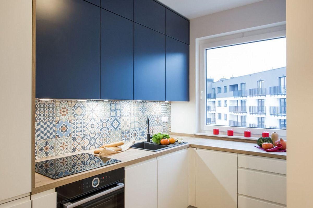 Pentru un aspect cât mai actual, mobila de bucătărie cu fronturi din MDF are mânere frezate, iar în partea superioară corpurile suspendate sunt până în tavan (corpuri care ascund și burlanul de evacuare pentru hotă). Corpurile suspendate sunt într-o nuanță înschisă de albastru, gândită în relație cu holul către dormitoare, care este vopsit într-o culoare similară.